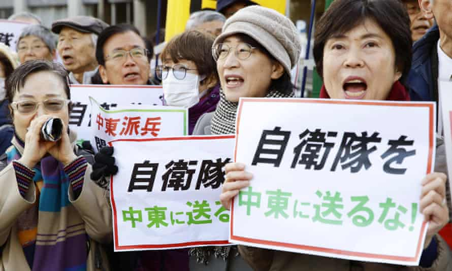 """Protesters in Tokyo with placards that read: """"Do not send Japan's self-defence forces to the Middle East."""""""
