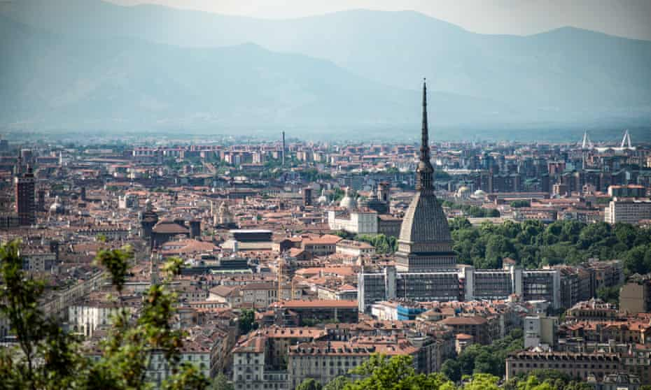 This cityscape of Turin takes in the Mole Antonelliana with its huge spire, surrounding buildings and mountains in the distance.