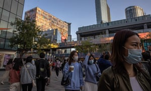 People wearing protective face masks visit the Sanlitun shopping area during the so-called 'Golden Week' public holidays, in Beijing, China, 4 October 2020.
