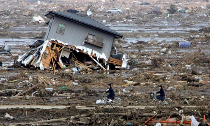 schoolgirls cycle through rubble in yamamoto japan after the 2011 tsunami