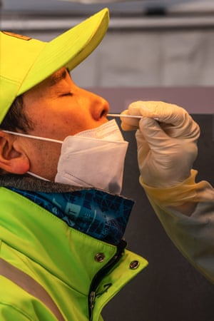 A man wearing a protective mask takes a nasal swab test at a temporary Covid-19 testing site in Seoul Square.
