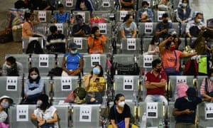People wearing protective face masks sit on social distancing benches at a bus station in, Thailand 22 March 2020.