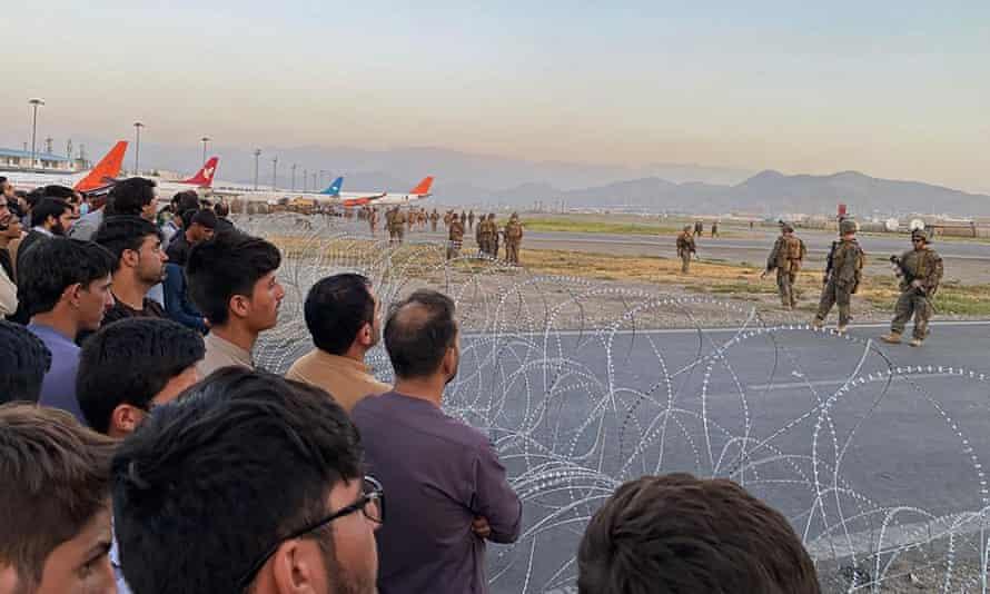 Afganos en la pista del aeropuerto de Kabul enfrentan alambre de púas y soldados estadounidenses en el otro lado