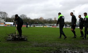 An Eastleigh groundsman brushes away the water as referee Iain Williamson does his third pitch inspection before allowing the game at the Silverlake Stadium to go ahead.