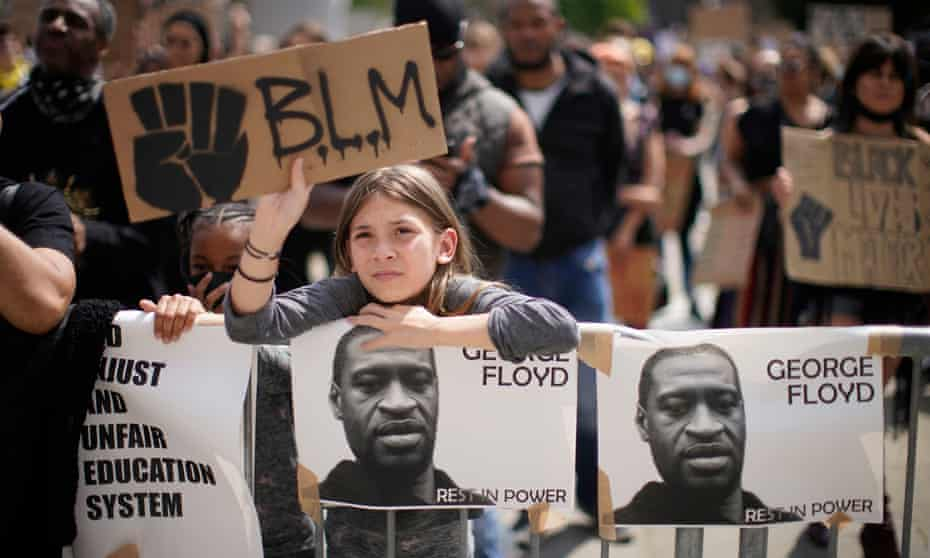 A girl holds up a BLM sign at a rally in Leeds