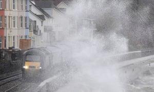 Large waves crash against the seawall during Storm Erik as a train passes through Dawlish