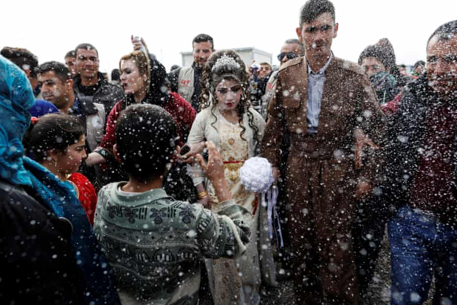 Hussain Zeeno Zannun, 26, and Chahad, 16, Iraqi newlyweds who fled Mosul, are showered in foam during their wedding party at Khazer camp in Iraq