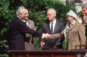 Peres shakes hands with a man in a keffiyeh while others in more conservative suits look on