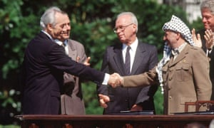 Yitzhak Rabin shaking hands with Palestinian leader Yasser Arafat at the White House in a deal brokered by Peres.