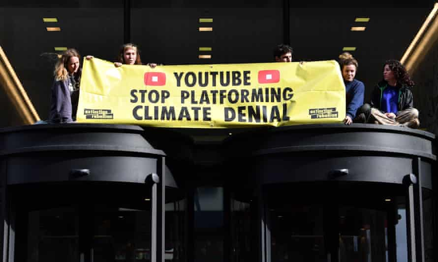 Young climate activists on the roof of the entrance to the Youtube offices in London.