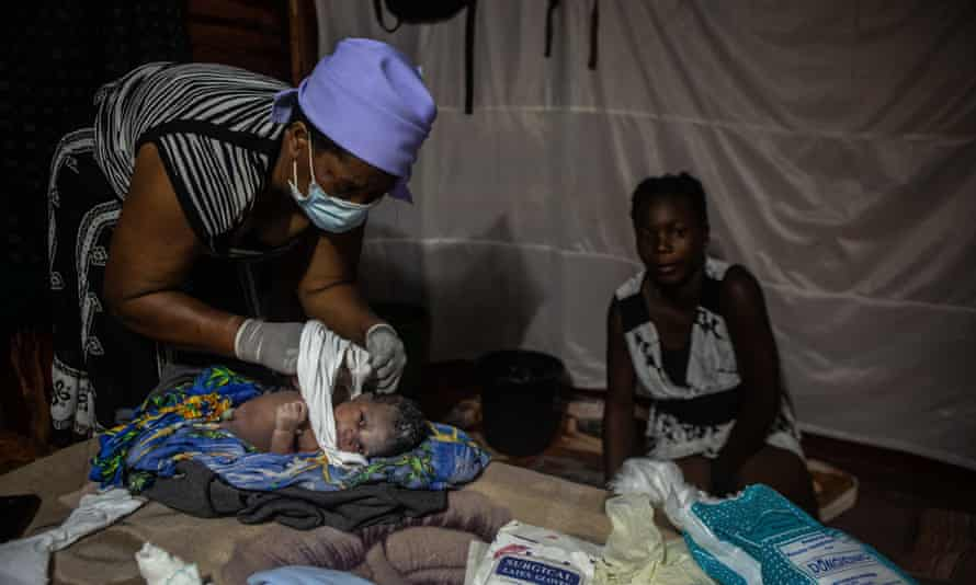 A midwife delivers a baby in Harare, 15 January. Covid has overwhelmed Zimbabwe's healthcare system after an economic crisis pushed the country into hyperinflation and poverty.