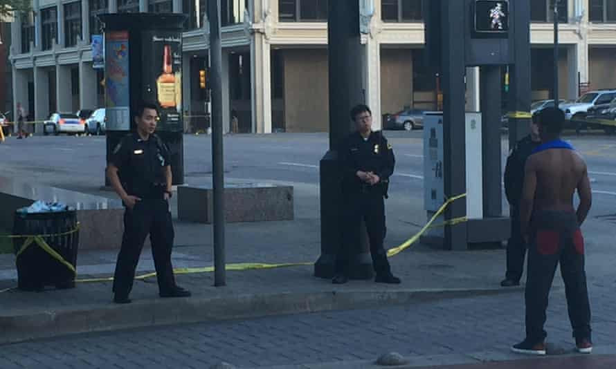 Three officers speak with a man in Dallas.