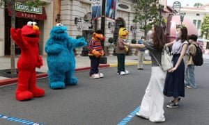 Sesame Street characters demonstrate how to greet visitors while keeping social distancing guidelines at Universal Studios Japan.