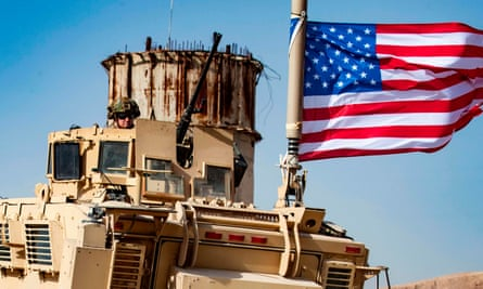 FILES-SYRIA-CONFLICT-TURKEY-KURDS-military(FILES) In this file photo taken on October 06, 2019 a US soldier sits atop an armoured vehicle during a demonstration by Syrian Kurds against Turkish threats next to a base for the US-led international coalition on the outskirts of Ras al-Ain town in Syria's Hasakeh province near the Turkish border. - The Pentagon said Sunday President Donald Trump had ordered the withdrawal of up to 1,000 troops from northern Syria -- almost the entire ground force in the war-torn country -- amid an intensifying Turkish assault on Kurdish forces. (Photo by Delil SOULEIMAN / AFP) (Photo by DELIL SOULEIMAN/AFP via Getty Images)