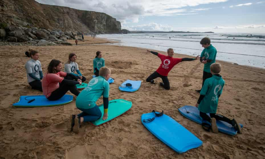A Wave Project instructor giving a surfing lesson at Watergate Bay in Cornwall