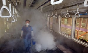 A worker disinfects a subway train carriage in Seoul.