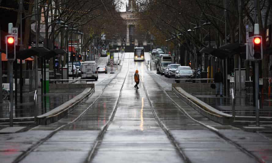 A person is seen crossing an empty Bourke Street in Melbourne