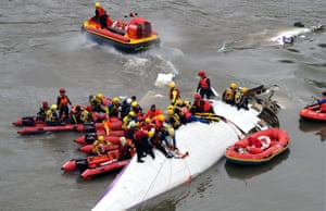 Search and rescue team members operate on a TransAsia Airways passenger plane crashed into the Keelung River in Taipei, Taiwan.