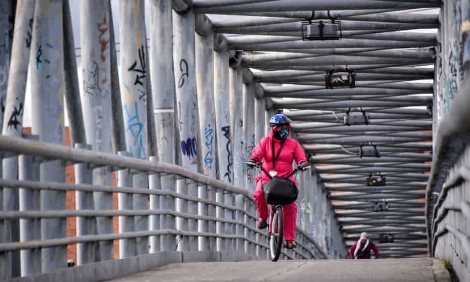 A woman wearing a face mask and a biosafety suit rides her bicycle as she crosses on a bridge at Kennedy in Bogotá in July.