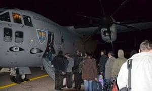 Romanian evacuees board a C-27J Spartan military airplane at Tripoli airport