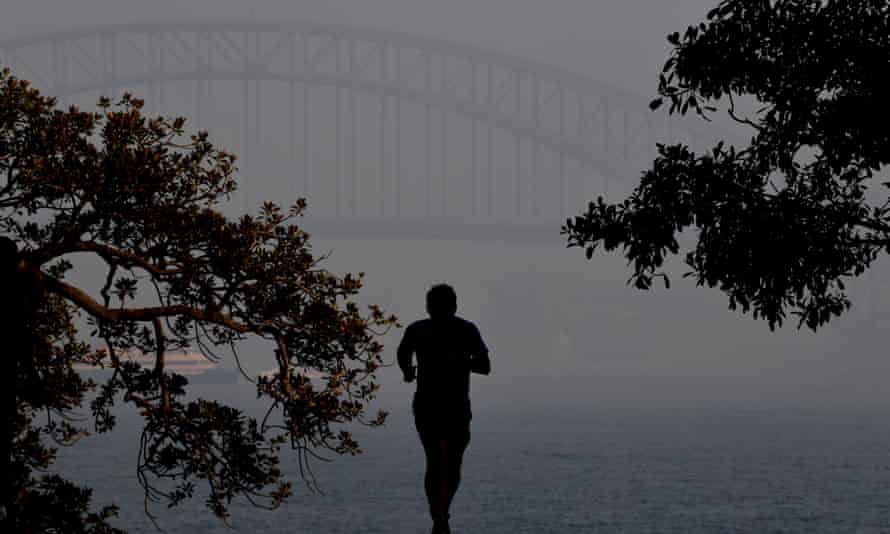 Person jogging in thick smoke obscuring the Sydney Harbour