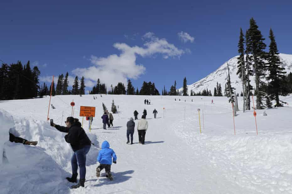 Visitors to Mount Rainier national park walk toward a sledding area.