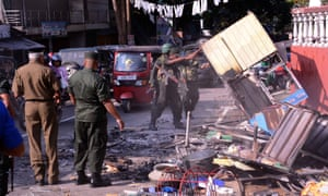 Sri Lankan security forces clean up a street in Kandy as a 10-day state of emergency is declared.