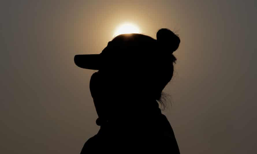 silhouette of woman in cap and mask against orange sky