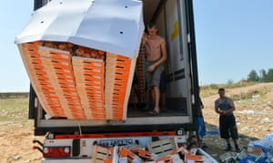 Workers throw peaches off a truck outside the city of Novozybkov