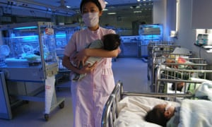 A nurse carries a newborn baby at a maternity ward in a hospital in China