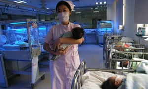 A nurse carries a baby at a maternity ward in  Wuhan, Hubei province.