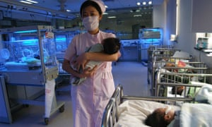 A nurse carries a newborn baby at a maternity ward in Wuhan, China.