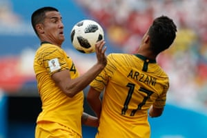 Australia's Tim Cahill and Daniel Arzani go for the ball.