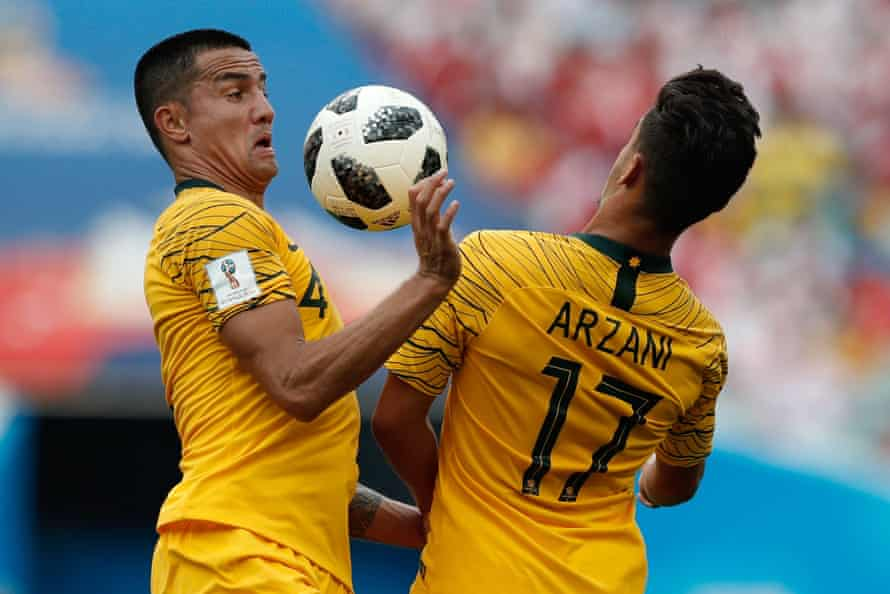 Australia's Tim Cahill and Daniel Arzani go for the ball.