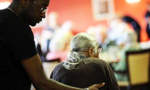 A care worker helps an elderly woman.