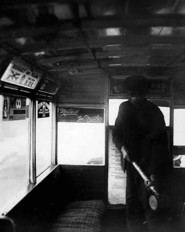 A man sprays the inside of a bus of the London omnibus with an anti-flu preparation in 1920.