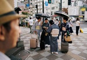 Tokyo, Japan: Women using sun umbrellas pause on a street during a heatwave