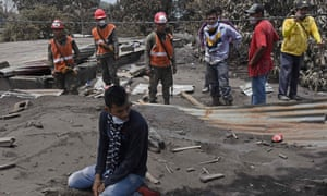Bryan Rivera, 22, cries as he searches for his relatives, victims of the Volcano of Fire eruption, in the ash-covered village of San Miguel Los Lotes on 7 June.