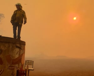 firefighter standing on water tank against glowing orange sky