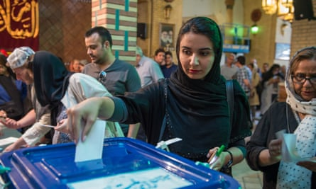 A voter casts her ballot at a polling station in Tehran