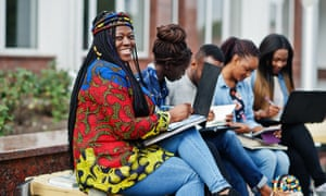 Group of five african college students spending time together on campus at university yard.