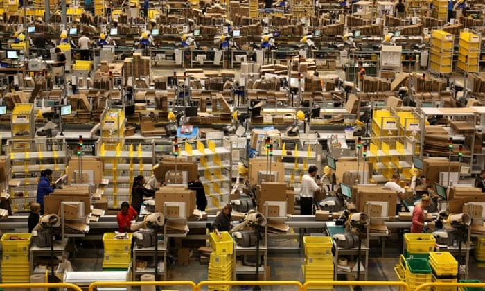 Workers pack orders at Amazon UK Fulfilment Centre in Peterborough, England.