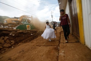 A girl in a communion dress walks past a demolition machine tearing down a house damaged by the earthquake.