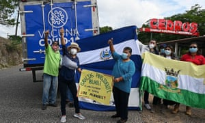 Residents hold banners thanking El Salvador's President Nayib Bukele for his donation of AstraZeneca vaccines against Covid-19, in Cedros municipality, Honduras.