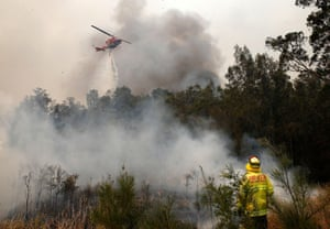 Firefighters work to contain a bushfire along Old Bar Road in Old Bar, NSW