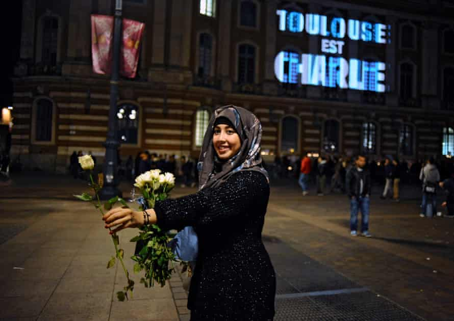 A woman holds out a white rose in Toulouse following the Charlie Hebdo attacks.