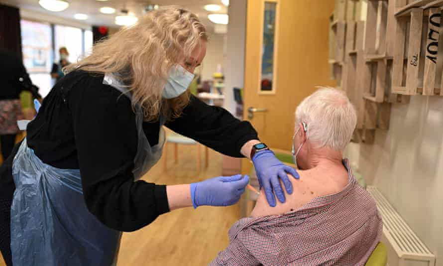 A man receives a dose of the Oxford/AstraZeneca Covid-19 vaccine at Belong Wigan care home in north-west England