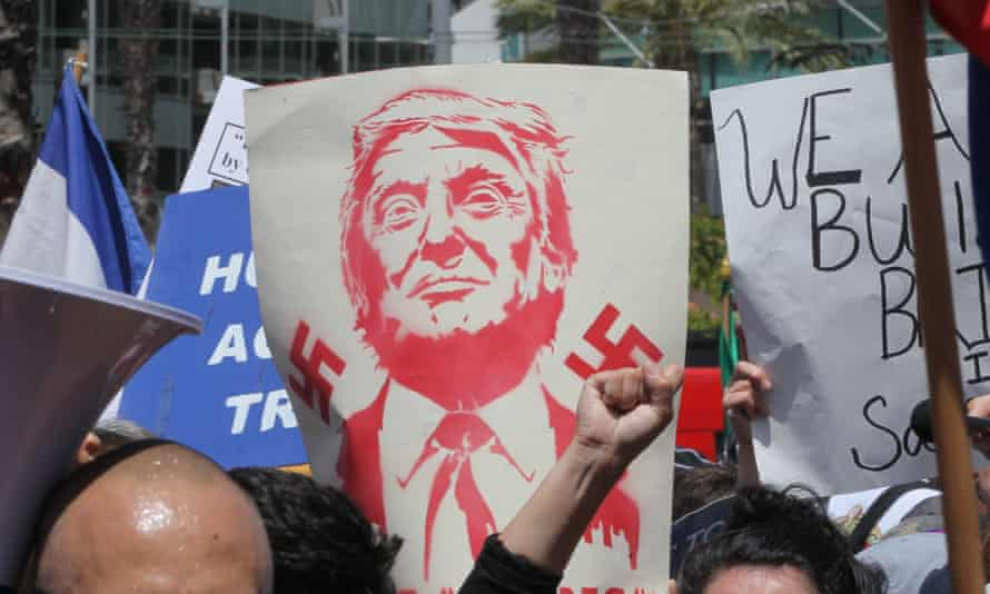 A protest sign with swastikas and Republican nominee Donald Trump, who has drawn sympathisers to the Ku Klux Klan and American Nazi Party.
