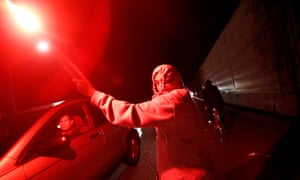 A protester holding a flare runs on Highway 580 in Oakland, California