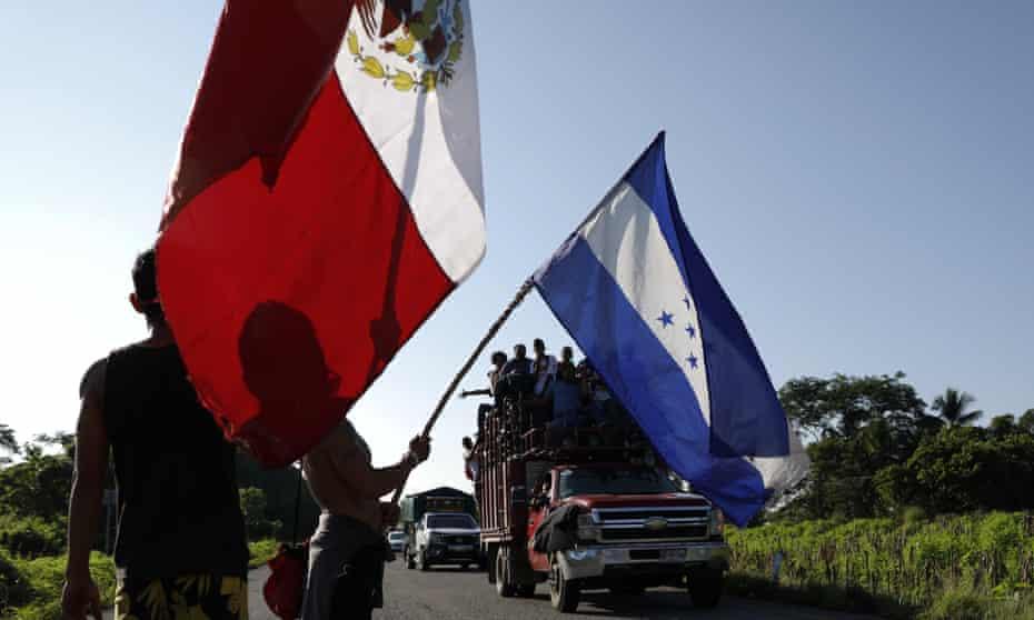 Honduran migrants walking north wave the flags of Honduras and Mexico.